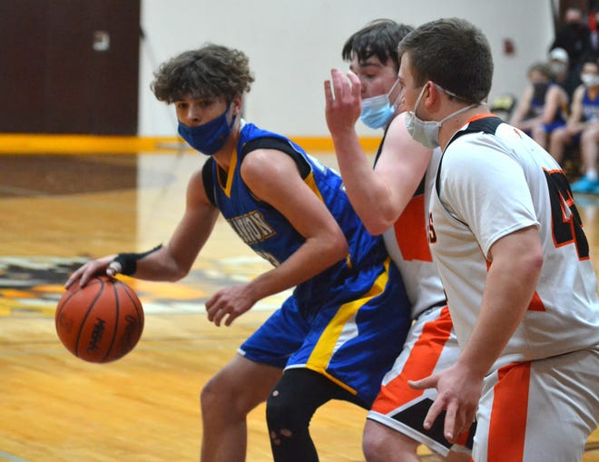 Alanson senior guard James Hungo (left) looks to find a way to the basket while Rudyard's EJ Suggitt and Cam Peterson defend during the first half of a Division 4 boys basketball regional final in Pellston on Thursday night.