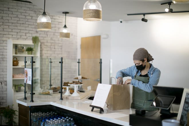Barista Kayla Williams fills an order at the new Freedom a la Cart Cafe + Bakery during its soft open on Thursday. Freedom a la Cart helps survivors of human trafficking by teaching practical skills such as cooking, along with life skills.