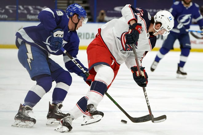 Tampa Bay Lightning left wing Ross Colton (79) knocks the puck away from Alexandre Texier (42) in the first period of the Blue Jackets' 3-2 loss Thursday in Tampa, Fla.