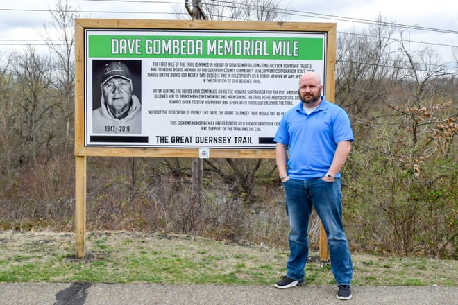 Ron Gombeda, director of the Guernsey County Community Development Corp., with the sign honoring his late father, Dave Gombeda. The Dave Gombeda Memorial Mile starts at the Corduroy Road trailhead of the Great Guernsey Trail, where numerous improvements are being made. Installation of an electric vehicle charging station and a new concession stand are just two of the updates to the area.
