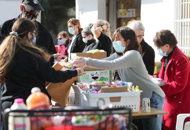Volunteers at the Jerry Doliner Food Bank in Ormond Beach, right, hand out groceries for Easter meals on Friday, April 2, 2021. The event was sponsored by the Jewish Federation of Volusia and Flagler Counties.
