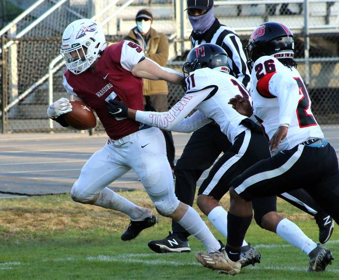 East Gaston's Justin Hill tries to break the tackle of East Rutherford's Nick Wingo during Thursday's game.