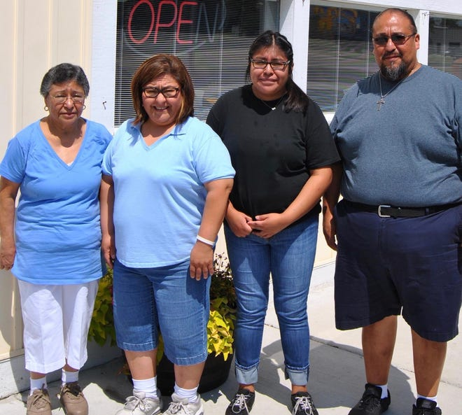 Margarita Salinas, left, poses for a photo with family in front of Margarita's Mexican Restaurant in Holland.