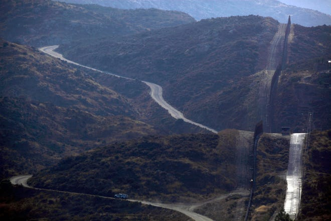 A patrol vehicle is seen from the Mexican side of the US-Mexico border, in Tecate, Saturday, July 25, 2009. (AP Photo/Guillermo Arias)