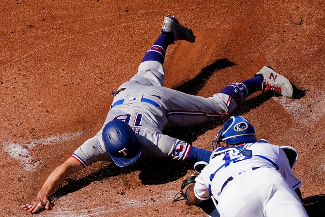 Texas Rangers' Brock Holt (16) is tagged out by Kansas City Royals catcher Salvador Perez trying to score on a single by Jose Trevino during the first inning of a baseball game Thursday, April 1, 2021, in Kansas City, Mo.