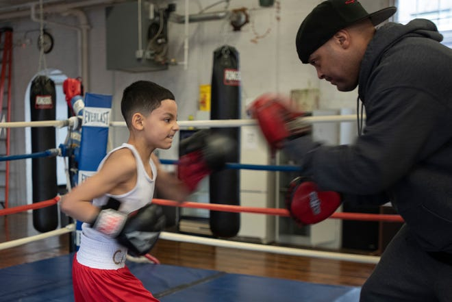 Carlos Cancel, Jr., 8, trains with his father, Carlos, in the boxing ring at Paladin Combat Sports in Clinton, April 1, 2021.