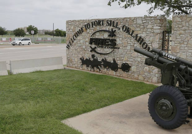A vehicle drives by a sign at Scott Gate, one of the entrances to Fort Sill.