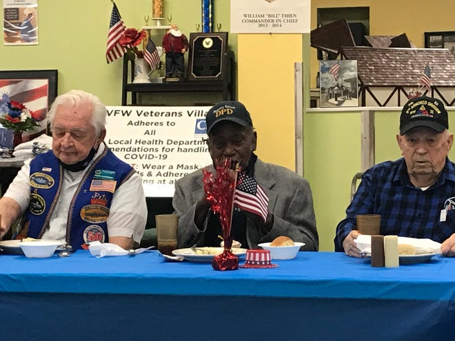 Clinton Burns, 99, center, talks about his World War II service at an event honoring veterans on Friday. At left is Peter Clemens and at right is Raymond Savoie.