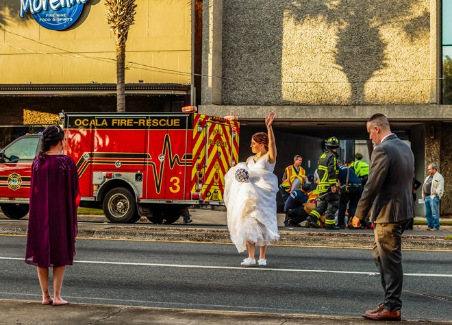 Marion County Sheriff's Corrections Officer Taylor Rafferty directs traffic with her wedding bouquet in hand as her future husband, MCSO Deputy Christopher Rafferty, right, responds to a vehicle vs. pedestrian crash on Dec. 12, 2020. The Raffertys were having pictures taken on the Ocala downtown square, just ahead of their wedding ceremony, when the crash happened. [Wendy McCarthy/Special to the Ocala Star Banner]2020