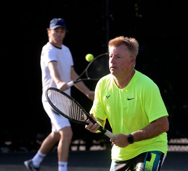Sam Garton waits for his friend Patrick Dillon to return a shot while playing doubles at the Phipps Ocean Park Tennis Center. Town staff is currently proposing a slight hike to annual, seasonal and 12-play tennis passes for both facilities.