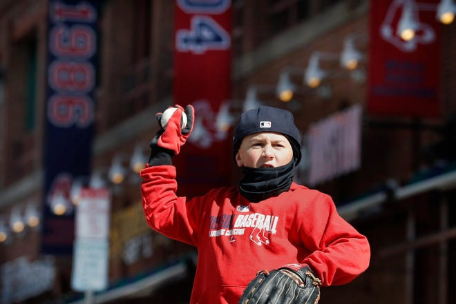 TJ Gonick, of Nutley, of New Jersey, plays catch with his father outside of Fenway Park before the Red Sox hosted the Baltimore Orioles on Opening Day on Friday.
