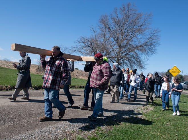 On Good Friday, four Rootstown church communities gathered to carry a cross through town. David Drennen of Rootstown, who made the cross, led the first leg of the walk, as well as Russ Bowman, Shawn Bruderly and Rae Hamilton. A group of about 25 followed during the first leg.