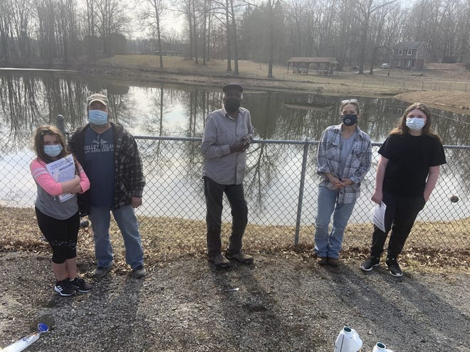 The Portage County Soil and Water Conservation District joined with the Skeels community to improve the pond next to the Skeels-Matthews Community Center. From left are Brie Bierlair with her father, James Bierlair, district  coordinator; James Worley Skeels community resident; and Lynn Vogel, storm water educator, with her son, Ben Lang.