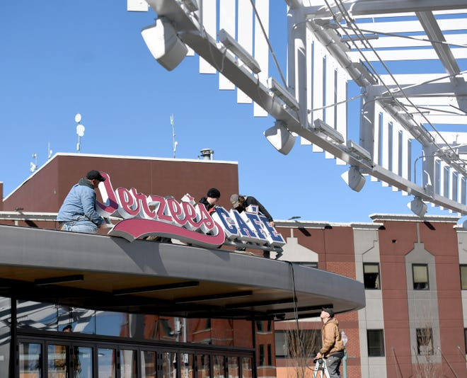 The installation crew with Akers Signs Company of North Canton work to install a sign on Jerzee's Cafe at Centennial Plaza in downtown Canton.