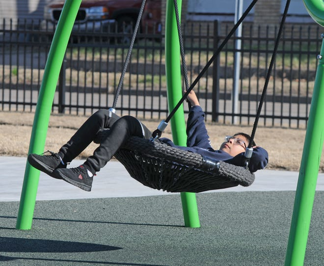 """Manuel Jimenez, 12, relaxes on one of the basket swings at Olivia's Playground, 323 Center St., in Salina. """"We had a long day today, so I came here to enjoy the nice weather we are having,"""" said Jimenez."""