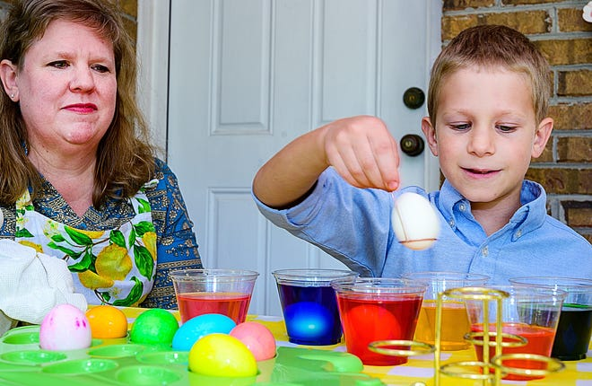 Patti Schiavo watches as her 8-year-old son, Matteo, dyes Easter eggs on the front porch of their home, south of St. Augustine, on Thursday.