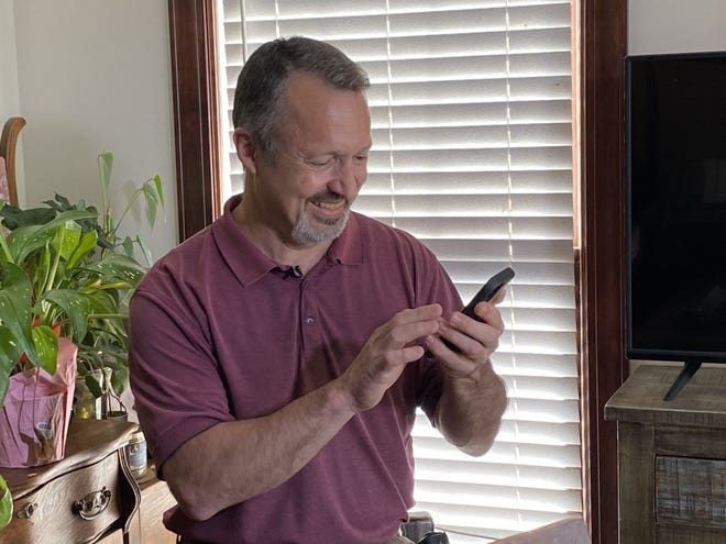 Wes Leonhardt smiles as he listens to his late mother's voice in a voice mail on his phone.