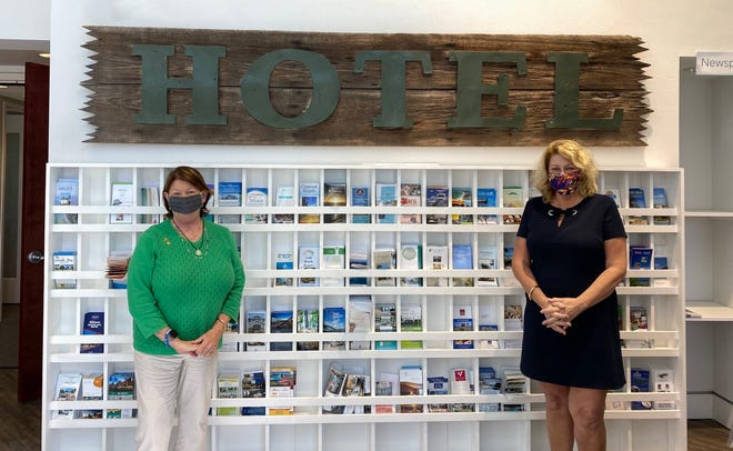 Virginia Haley, president of Visit Sarasota County, and Bobbi Ellis, sales manager at The DeMarcay Residences, with the donated hotel sign.