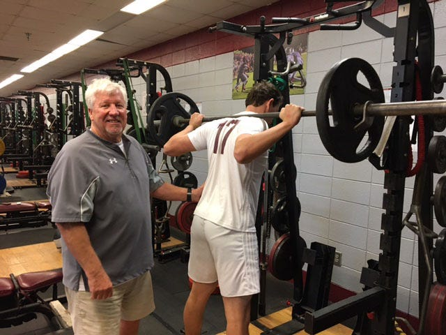 Former South Effingham football coach Mike Harper helps Mustangs football player Matt Dye during weightlifting class. Harper has been filling in after strength coach Mike Pfiester accepted a head football coaching job at Long County High School.