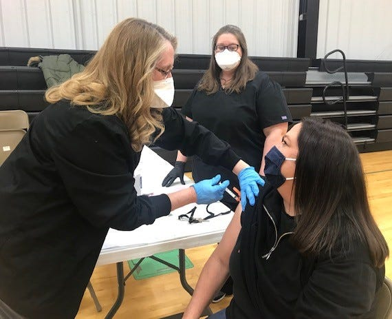 Henry and Stark County Health Department Nurse, Heather Aldred, RN administers the Covid-19 Vaccination to Kewanee School District Teacher, Shana Hinton as Tara DeBlieck of the Kewanee School District and the Health Department looks on.