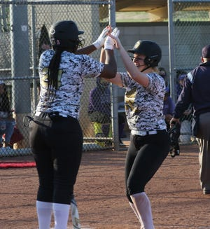 Zoe Caryl (right) high-fives Topeka High teammate NiJaree Canady (left) after belting a three-run home run in the second inning of Thursday's second game with Topeka West at Hummer Sports Park. Caryl also hit a bases-loaded double in High's 12-run inning in a 19-3 win.