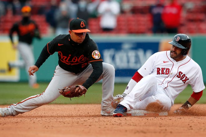 Boston's J.D. Martinez, right, slides safely into second base on his double ahead of the throw to Baltimore's Ramon Urias.