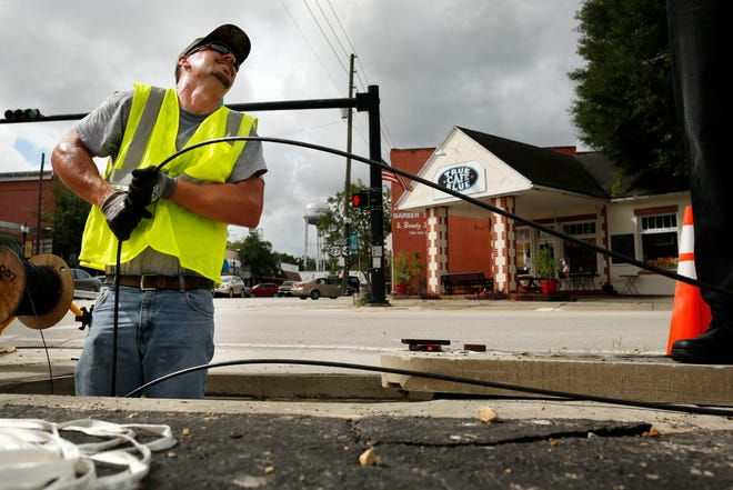 A network cabling specialist with GRUCom pulls fiber optic cable during an install for the High Springs branch library in 2015.