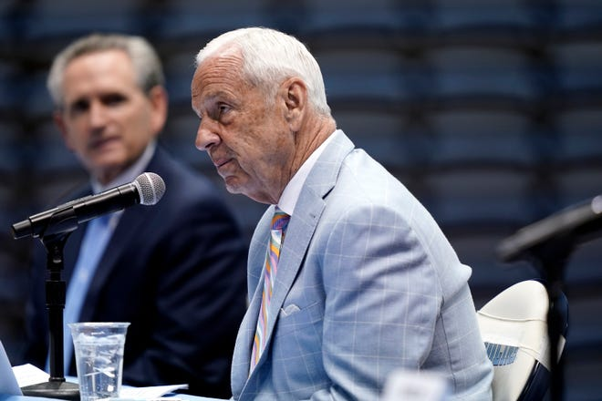 North Carolina athletics director Bubba Cunningham, left, looks on as coach Roy Williams speaks during Thursday's news conference announcing his retirement.