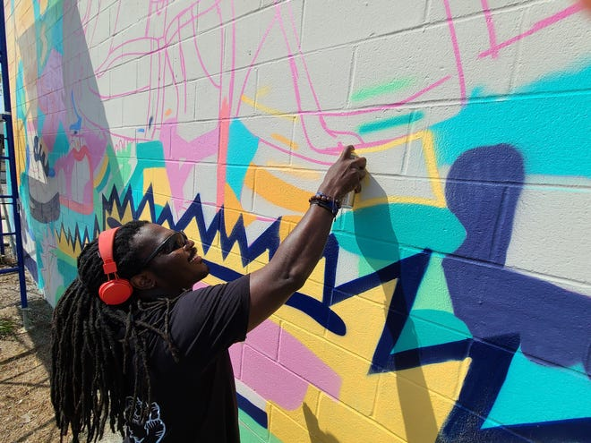 George F. Baker III is seen at work on a mural off Grace Avenue in downtown Panama City this week.