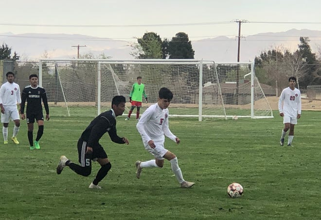 Oak Hills' Omar Vela dribbles the ball while defended by Hesperia's Victor Amaro on Thursday afternoon.