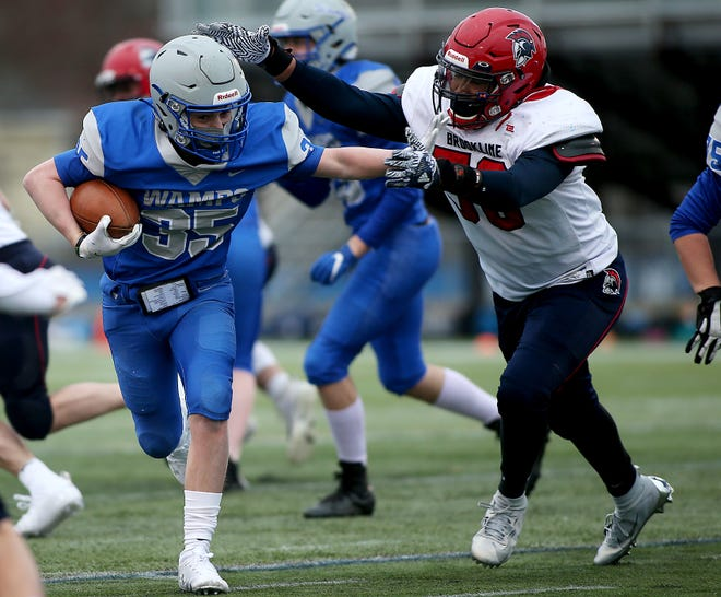 Braintree's Henry Joyce looks to escape the grasps of Brookline's Damian Halfkenny during a rush in the second quarter of their game at Braintree High on Thursday, April 1, 2021.