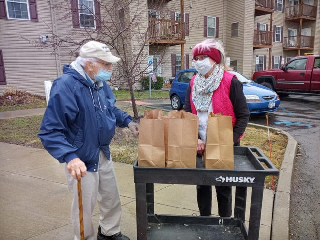 Ron Depersis, left, receives a delivery of groceries from Joan Sprague, who is a longtime volunteer for Faith in Action, which has had to revamp some of its services due to the ongoing COVID-19 pandemic.
