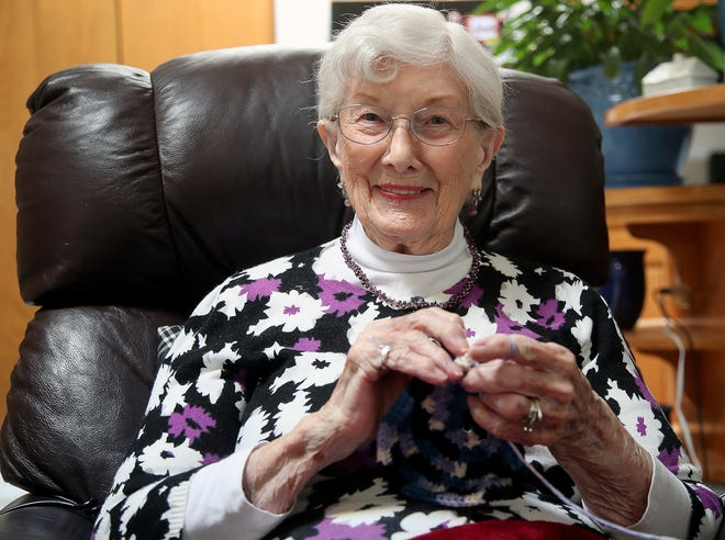 "Edith Stanley looks up and smiles as she crochets a hat at her home on Friday. Stanley said crocheting keeps her mind active. ""At this age, you need something."""