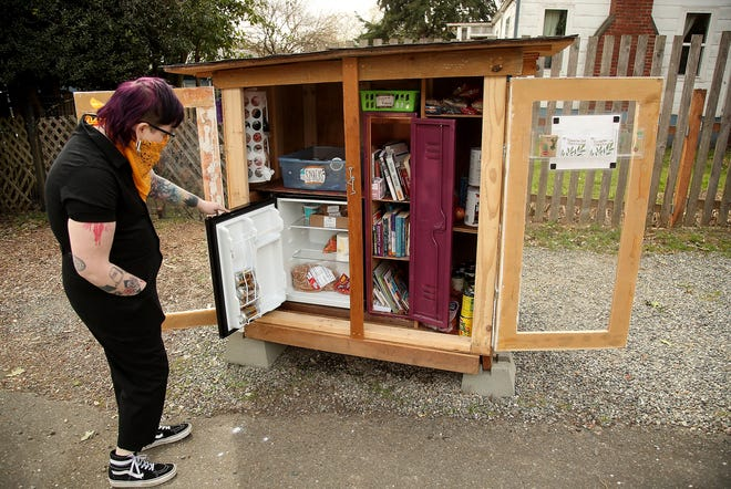 Ollie Fjor'skera opens the mini-fridge inside the free pantry they built and placed outside their Bremerton home on Friday. The pantry features food, books and hygiene products.