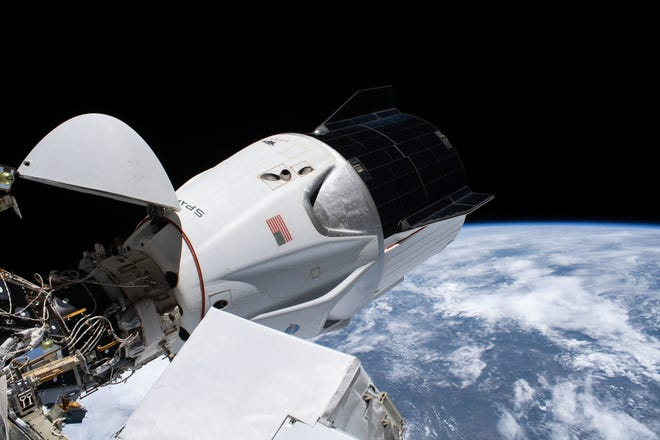 The SpaceX Crew Dragon capsule used for the Crew-1 mission, named Resilience, is seen attached to the International Space Station's Harmony module.