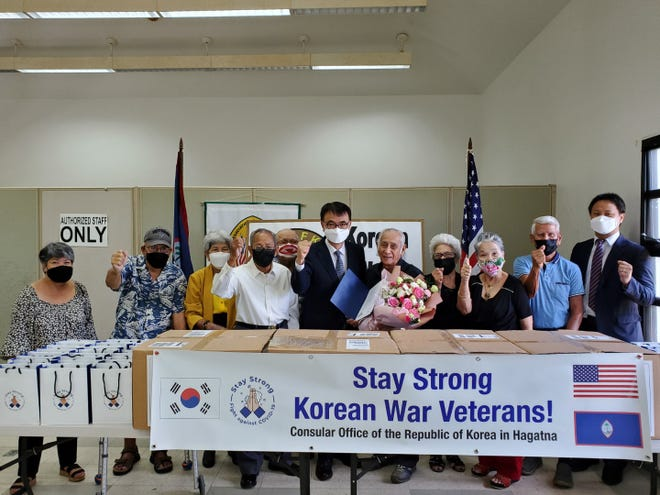 Members of the Korean War Veterans Association of Guam gather to take a picture with Head of Mission In Kook Kim and Consul Kyungbo Jeong before they are presented with Mask Care Packages to take home.
