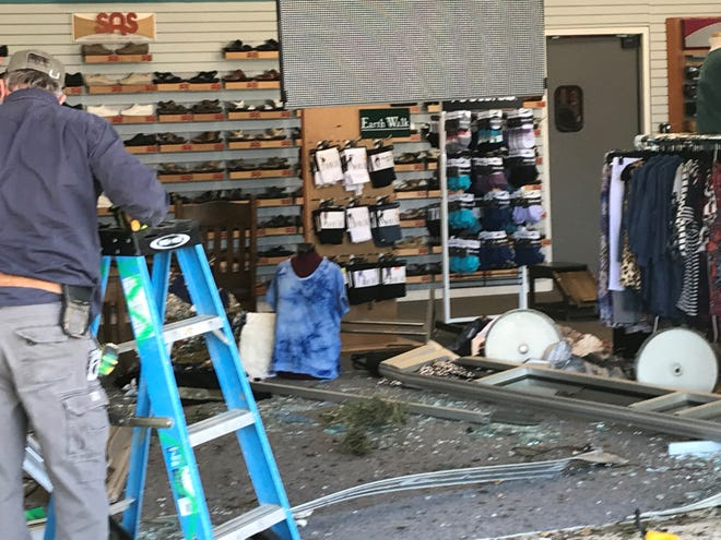 Crews begin repair work to the storefront of Earth Walk Shoes, located at 2323 Lakeland Drive in Flowood, Mississippi, on April 2, 2021. A woman reportedly crashed her truck into the store, leaving one person injured.
