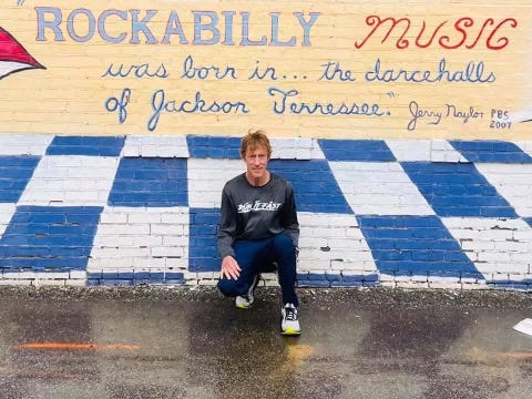 Randy Broadway poses for a picture in front of the mural at the Rockabilly Hall of Fame and Museum building in Downtown Jackson.