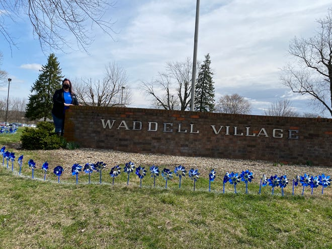 Foster Care & Community Engagement Coordinator Elizabeth Moore stands besides a sign for Waddell Village, which was the previous name for MCCS. Moore helped out in the pinwheel planting held Wednesday, March 31, 2021.