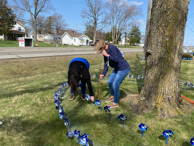 Executive Director Jacqueline Ringer, right, and a staff member plant pinwheels around a tree for MCCS' annual pinwheel planting Wednesday, March 31, 2021.