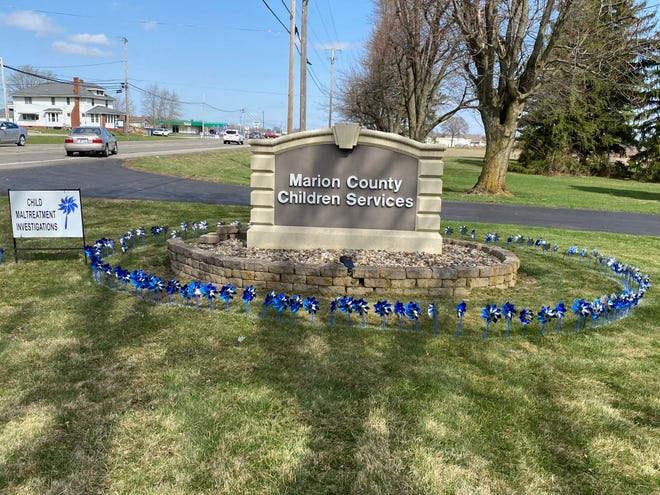 A ring of pinwheels circle the entrance sign for Marion County Children Services. The objects represent the number of child abuse cases the agency handled last year, which was 794.