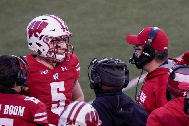 Wisconsin head coach Paul Chryst talks to quarterback Graham Mertz during the first half of a game against Indiana on Dec. 5, 2020, in Madison.