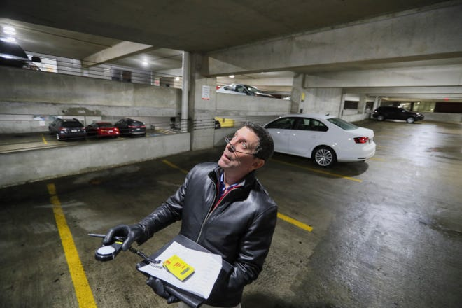 Security expert Randy Atlas uses a light meter to check lighting levels in a parking garage on March 17, 2021, at Ascension Columbia St. Mary's Hospital in Milwaukee.