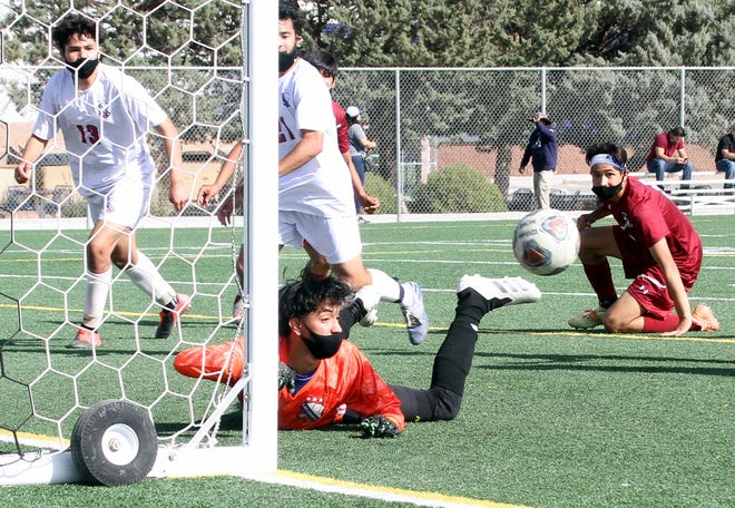 Junior Wildcat forward Kevin Martinez (kneeling) eyes his shot that caromed off the goal post during the first half of Deming's 5-0 victory over Las Cruces High.
