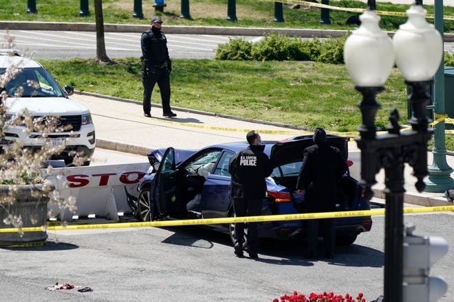 U.S. Capitol Police officers stand near a car that crashed into a barrier on Capitol Hill in Washington, Friday, April 2, 2021.