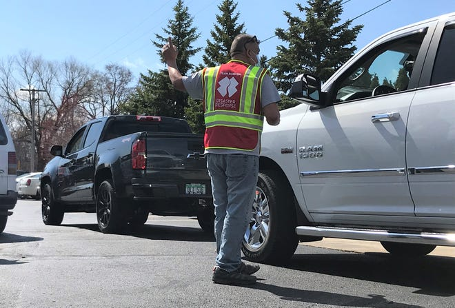 Team Rubicon volunteer Joey Munoz, of Emmett, directs incoming vehicles at the St. Clair Health Department's COVID-19 vaccine clinic on Wednesday, March 31, 2021, in Marysville.