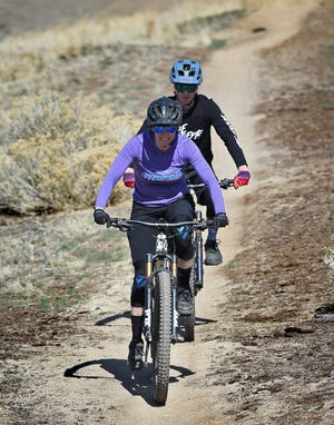 Amanda Wentz, front, and Rick Reed ride e-bikes on April 2, 2021.