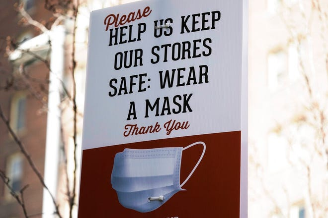 """A sign requiring face masks is seen at Harmons Grocery store Monday, March 8, 2021, in Salt Lake City. Utah on Tuesday ended mandated limits on gatherings and social distancing related to the coronavirus after the state reached several metrics laid out in a so-called """"COVID-19 endgame"""" bill passed earlier this year."""