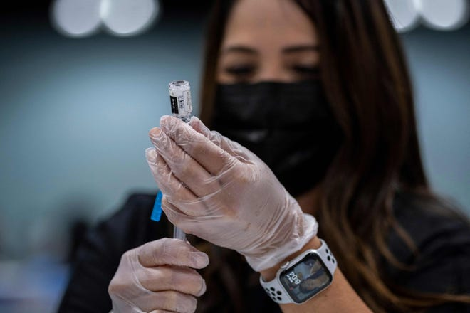 A health worker prepares a dose of the Johnson and Johnson Covid-19 vaccine at the Puerto Rico Convention Center during the first mass vaccination event in San Juan, Puerto Rico on March 31, 2021.