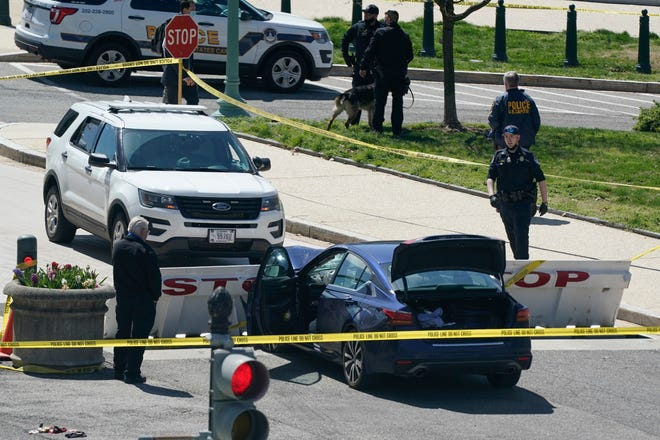 U.S. Capitol Police officers stand near a car that crashed into a barrier on Capitol Hill in Washington on Friday.
